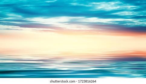 Fondo de un paisaje de mar. Cielo azul con nubes sobre el mar. Luz del sol, puesta de sol