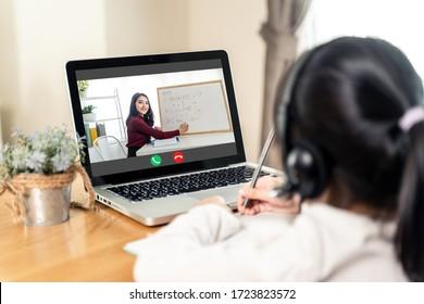 Homeschool Aziatisch klein jong meisje leert online klas van schoolleraar door externe internetvergaderingstoepassing vanwege coronavirus pandemie. Vrouw die wiskunde onderwijst met behulp van hoofdtelefoon en whiteboard.
