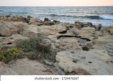 日没時の岩の多い海岸、岩に砕ける波、雷雨の前に暗い夕焼けの空の反射で岩の自然によって形成された小さなプール