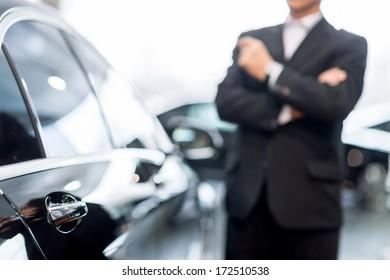 ディーラーで車を選ぶ。車で傾いているとよそ見正装で思いやりのある白髪の男