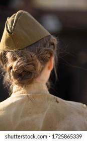 meisje in uniform staat met haar rug op een grote zeis