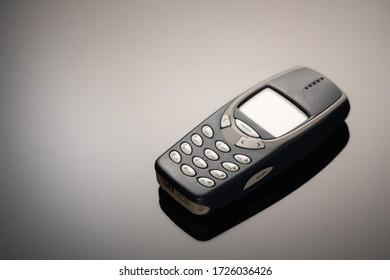 Ein veraltetes Mobiltelefon mit einem Bildschirm zum Kopieren von Speicherplatz auf einem grauen Verlaufshintergrund. Der minimalistische Trend. Smartphone. mit Kopierraum für Text.