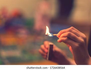 Das Kind zündet die Streichhölzer an. Das Feuer in den Händen eines Kindes. Ein kleines Kind spielt mit Streichhölzern, einem Feuer, einem Feuer, Gefahr, Kind und Streichhölzern, Luzifer-Streichholz. getönt
