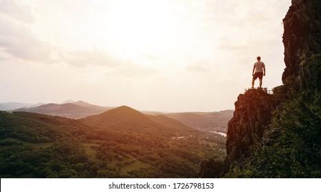 Ein Mann, der auf einem Berg steht, als die Sonne untergeht. Ziele und Erfolge Konzept Foto Composite. Konzeptvision, Wanderer, der Berg schaut und Sonnenaufgang genießt
