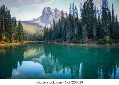 Schöne Aussicht auf Mount Burgess am Emerald Lake in British Columbia. Klares türkisfarbenes Wasser reflektiert den schneebedeckten Berg, hohe Kiefern, die das Ufer säumen, und weiße Wolken in einem blauen Himmel.