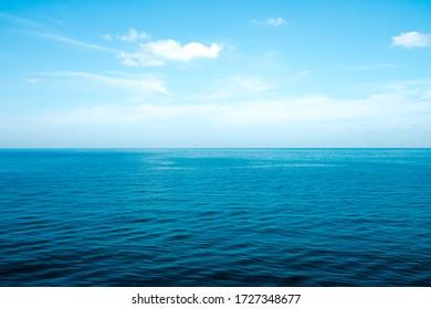 明け方の空の正面図は明るい青で、澄んだ白い雲があります。そして、日光の下で海の深い藍色。落ち着き、涼しさ、リラックス感。冷たい背景と上部のコピースペースのアイデア。