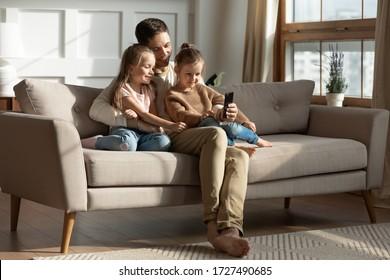 Lächelnder Vater mit zwei kleinen Töchtern, die Telefon benutzen, Bildschirm betrachten, Zeichentrickfilme oder Video ansehen, Spiel spielen, online einkaufen, niedliche Vorschulmädchen mit Papa umarmen, auf Couch zu Hause sitzen