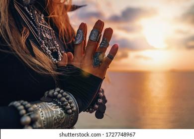 cerca de las manos de la mujer. mujer de estilo tribal en la playa al atardecer