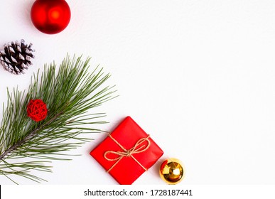 Fichtenzweig, rotes Geschenk, Weihnachtsbaumspielzeug und Beule. Minimalismus. Kopierraum