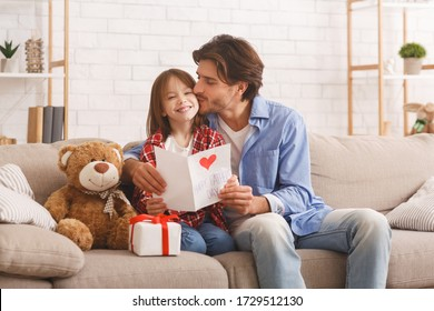 The best present is you. Happy daddy kissing his smiling little daughter on Father Day, home interior, copy space