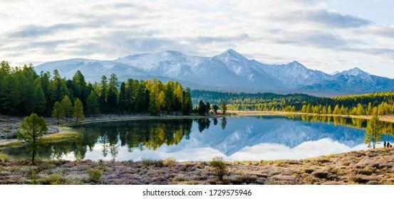 Lago Cicely Altai, Siberia, nublado día de otoño. Taiga, hermoso cielo, neblina, montañas con picos nevados, panorama.
