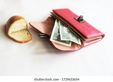 The last two dollars for bread were left in the red purse. Layoffs and unemployment, low purchasing power of the population. The red purse is open, containing two US dollars and two pieces of dry brea