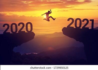 シルエットの男は日没の背景、成功新年のコンセプトで2020年から2021年の間にジャンプします。