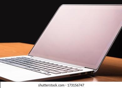 木製の机の上でラップトップを開く