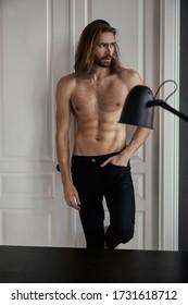 あごひげとクールな長い髪のハンサムな残忍な男。セクシーなトップレス。自信を持って、魅力的で、スタイリッシュ。ファッション撮影。俳優。