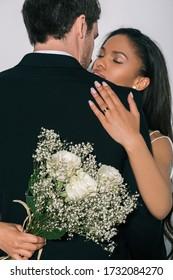 白で隔離の結婚式の花束を保持しながら新郎を抱き締める美しいアフリカ系アメリカ人の花嫁