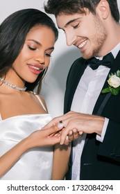 白い背景の上の幸せな新郎の指に結婚指輪を置く美しいアフリカ系アメリカ人の花嫁