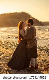 Romantic viking's reenactment couple at sunset on the beach and mountains background