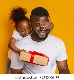 Father's day. Cheerful little afro daughter hugging her dad, closing his eyes and giving gift box, orange background