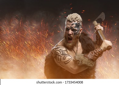 Medieval warrior berserk Viking with tattoo and in skin with axes attacks enemy in fire background
