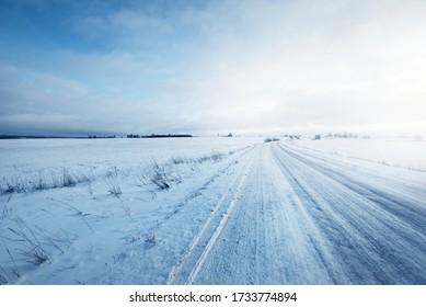 Carretera nacional cubierta de nieve a través de los campos después de una tormenta de nieve al atardecer. Antigua casa rústica al fondo. Escena rural de invierno. Cielo dramático, celaje colorido. Desierto de hielo. Laponia, Finlandia