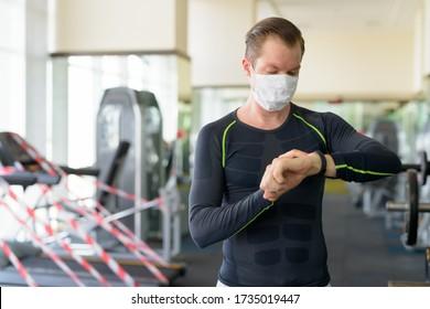 コロナウイルスcovid-19の間にジムでスマートウォッチをチェックするコロナウイルスの発生から保護するためのマスクを持つ若い男