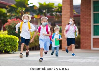 Schulkind mit Gesichtsmaske während des Ausbruchs des Koronavirus und der Grippe. Jungen und Mädchen gehen nach der Quarantäne und der Sperrung wieder zur Schule. Gruppe von Kindern in Masken zur Vorbeugung von Coronaviren.