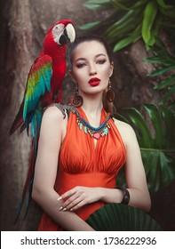 Porträt der jungen attraktiven Frau im afrikanischen Stil mit Ara Papagei auf ihrer Hand auf einem tropischen Hintergrund. Schönes brünettes Mädchen in Drungles mit einem Ara-Papagei. Künstlerische Verarbeitung.