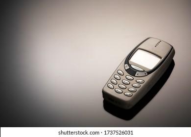 Ein veraltetes Mobiltelefon mit einem Bildschirm zum Kopieren von Speicherplatz auf einem grauen Hintergrund mit Farbverlauf. Der minimalistische Trend. Smartphone. mit Kopierraum für Text.