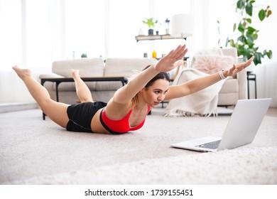 Fit Frau, die Supermans Übung macht und Online-Workout-Tutorial auf Laptop, Training im Wohnzimmer sieht