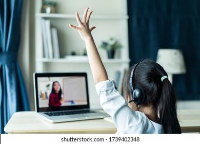 Homeschool Aziatisch klein jong meisje student leert virtuele internet online klas van schoolleraar door externe vergadering vanwege covid pandemie. Vrouw die wiskunde onderwijst met behulp van hoofdtelefoon en whiteboard.