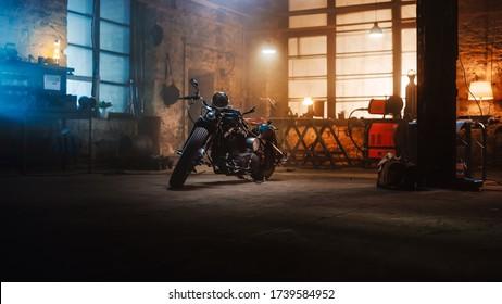 Moto Bobber personalizada de pie en un auténtico taller creativo. Motocicleta de estilo vintage bajo la cálida luz de la lámpara en un garaje.