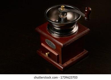 Manual coffee grinder for grinding coffee beans. Black background. Vintage coffee grinder