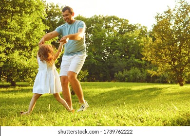 Father's day. Father plays with his daughter in the summer park.