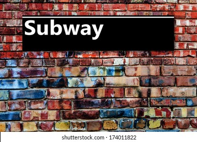 Subway or Underground sign board on a graffiti laden brick wall