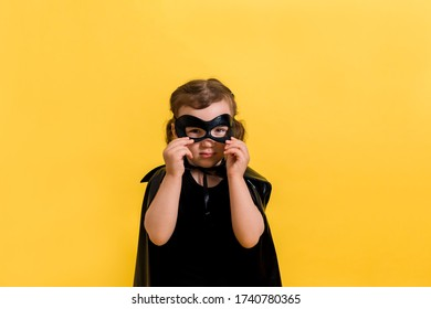 Portrait of a little girl in a suit with a black mask on a yellow background with space for text