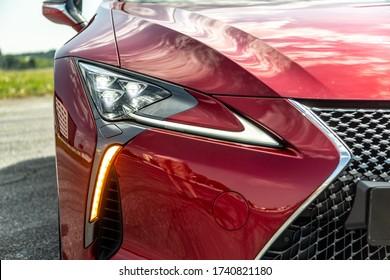 Kühlergrill und Scheinwerfer an einem roten Auto an einem sonnigen Tag. Nahaufnahme. Horizontale Ausrichtung.