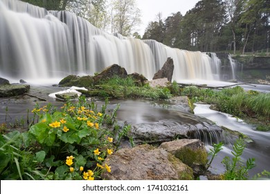 Waterfall in the lower course of the Keila River on North Estonian Klint.  Keila-Joa Castle Schloss Fall (Keila Joa . Smooth surface, broken and fallen rocks and grass, cloudy skyscape. Estonia.