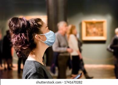 Schutz vor dem Virus. Ein Tourist besucht die Sehenswürdigkeiten des Museums in einer medizinischen Maske. Menschen und Bilder im Hintergrund. Das Konzept einer Viruspandemie und der Aufrechterhaltung der Distanz