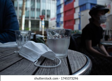 A protective mask lies on a table in a cafe and next to it is a glass of water. Masks can cause dehydration and difficulty breathing in hot weather. When you wear a mask in the summer you need water.