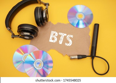BTS concept with headphones and music discs on a yellow background.