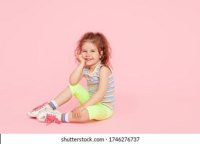 ピンクの背景の上の驚きのかわいい幼児の女の子の子供の肖像画。カメラを見てください。手を左側に向けます。子供向け商品の宣伝
