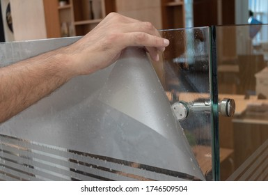 Primer plano de detalle de aplicación de película para ventanas esmerilada. Mano de hombres expertos