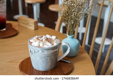 Hot Cocoa with a marshmello put on wooden table. Dried flower in a blue vase.