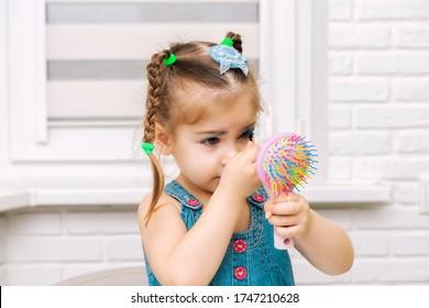 青いドレスを着た未就学児の少女は、青い影で目を塗ります。