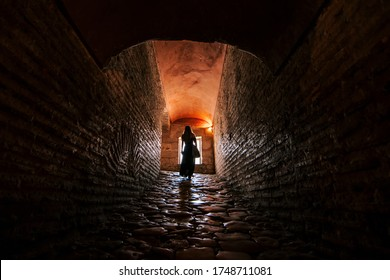 girl walking in a tunnel with a window in the background. Long tunnel. death
