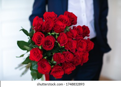 Bouquet of red roses at the man's hands in blue suit on white background. Copy space