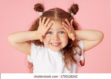 Porträt des überraschten niedlichen kleinen Kleinkindmädchenkindes über rosa Hintergrund. Kamera betrachten. Zeigt mit den Händen auf die linke Seite. Werbung für Kinderprodukte
