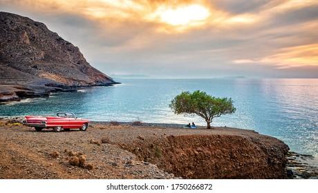 Das Foto der erstaunlichen Landschaft von Kreta mit dem roten Retroauto andlonely Baum, Sonnenuntergang und Meerblick