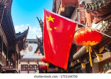 Rote Nationalflagge von China gegen alte chinesische Gebäude am Yuyuan-Garten in Shanghai, China